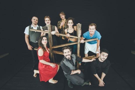 Fotografia colorida dos oito artistas circenses do grupo Cia Los Circo Los, seis homens e duas mulheres, todos sorridentes, ao redor de uma estrutura de madeira com canaletas transversais. Cinco artistas estão em pé e três estão abaixados.