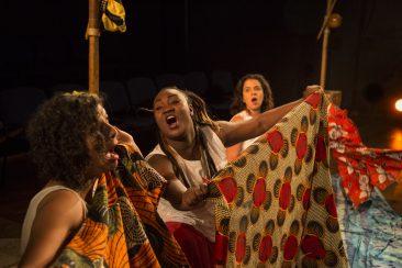 Fotografia colorida, da cintura para cima, de três mulheres, uma ao lado da outra, segurando tecidos coloridos esticados à frente do corpo, com as bocas abertas, como se cantassem. As duas da ponta também seguram berimbaus.