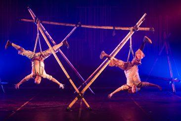 Fotografia colorida de dois acrobatas pendurados de cabeça para baixo com cordas, em estruturas de bambu amarradas e cruzadas. Os dois estão com as pernas e os braços abertos, no palco iluminado com luz azul.