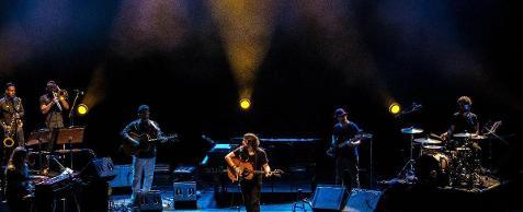 Fotografia colorida dos sete componentes da banda no palco tocando seus instrumentos. Na frente, bem no centro, Teago Oliveira toca violão, do lado esquerdo, Xuxa Levy está sentado no teclado, no meio do palco, à esquerda, Regis Damasceno na guitarra, à direita, Dudinha Lima no baixo, e ao fundo, do lado esquerdo, Denilson Martins na flauta, Will Bone no sax e do lado direito, Davi Gomes na Bateria. Uma luz tênue azulada ilumina o palco e, ao fundo, três holofotes projetam um feixe de luz amarela para o alto.