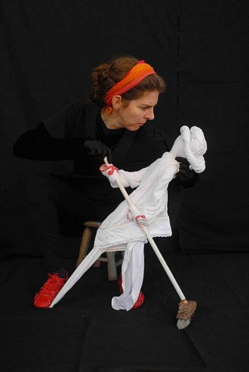 Fotografia colorida de Andi manipulando uma boneca feita de panos brancos, que segura uma vassourinha. Andi é uma mulher de pele clara, olhos verdes, cabelos louros presos e com uma faixa laranja. Ela usa roupas pretas e tênis vermelhos e está sentada em um banquinho, no palco forrado de preto.