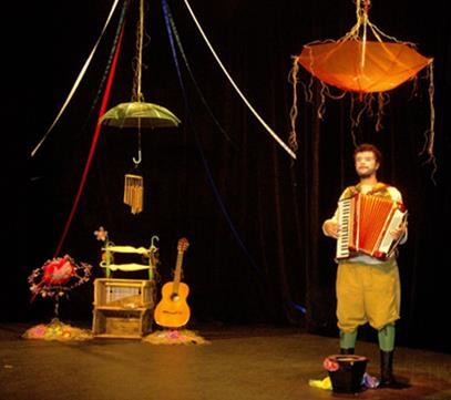 Fotografia colorida de um rapaz tocando sanfona, à direita do palco, com um balde à frente. Ele tem a pele clara, os cabelos louros cacheados, barba e bigodes. Usa camisa branca e bermuda amarela, meias verdes e botas pretas. No teto dois guarda-chuvas abertos e pendurados, um laranja e outro verde, um com sinos de bambu presos no cabo, outro com fitas coloridas que vão até o chão. À esquerda, alguns objetos como um arranjo de flores, dois caixotes de madeira e um violão no pedestal.