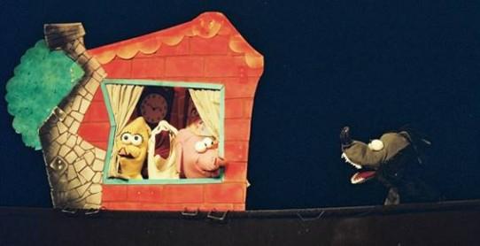 Fotografia colorida de quatro bonecos do espetáculo Os três porquinhos. Os três porquinhos, um amarelo, um branco e outro cor-de-rosa estão na janela de uma casinha de tijolinhos com chaminé e árvore ao fundo. Do lado de fora, à direita, um lobo preto de olhos esbugalhados e boca escancarada olha para eles.  Os porquinhos têm olhos arregalados e focinho comprido. O porquinho amarelo olha ao longe, o porquinho branco abre a boca, e o cor-de-rosa olha curioso para o lobo que se aproxima.