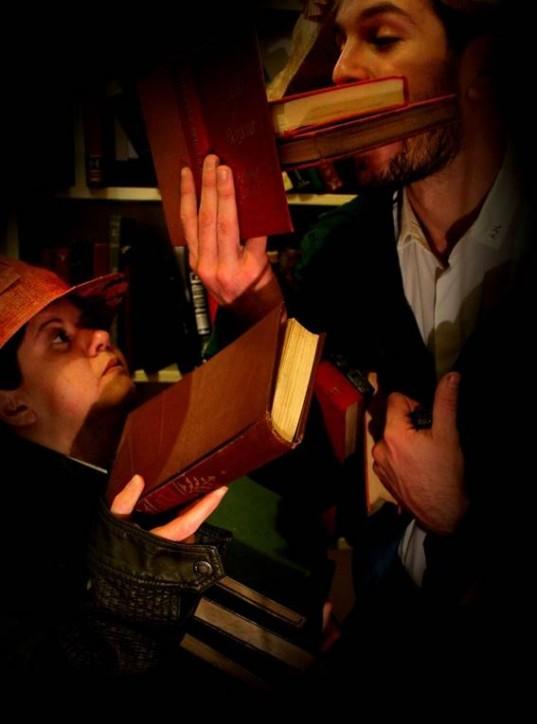 Fotografia colorida, em plano médio (da cintura para cima), do soldado de chapéu laranja e jaqueta preta (interpretado por Marília Scofield), segurando uma pilha de livros e entregando para o Capitão Bigode de Limão (interpretado por Carlos Escher). O Capitão com barba e bigode, de paletó verde, apoia dois livros na boca e em um livro aberto.
