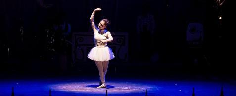 Fotografia colorida de uma bailarina em pé no meio do picadeiro com um braço em arco acima da cabeça, o outro dobrado à frente do corpo, uma perna na frente da outra, o pé virado para fora. Ela usa titi branco, saiote armado de tule, com corpete no mesmo tom. Um foco redondo de luz ilumina-a.