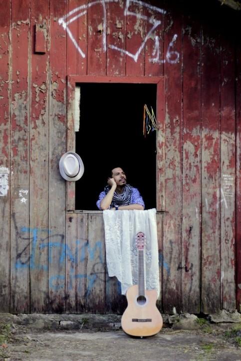 Fotografia colorida de Eduardo Agualuz apoiado numa ampla janela de uma casa de madeira avermelhada, descascada e pichada. Eduardo olha para fora pensativo, com rosto apoiado na mão. Ele é um homem moreno, de cabelos castanhos escuros curtos, bigodes e cavanhaque. Veste camisa e lenço xadrez. Uma toalha branca de renda está estendida na beira da janela quase arrastando no chão de terra batida, onde está um violão. Um chapéu panamá branco está pendurado na moldura da janela à esquerda e algumas fitinhas coloridas estão presas em varetas à direita.