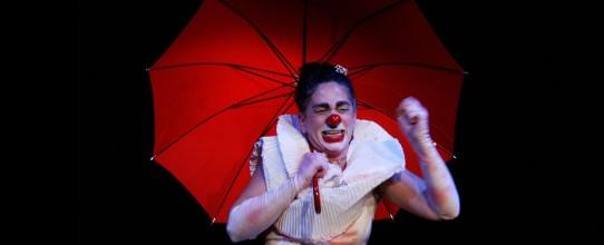 Fotografia colorida na horizontal em plano médio sobre fundo escuro da palhaça Mafalda Mafalda, interpretada por Andréa Macera, segurando um guarda chuva vermelho, com a boca entreaberta e os olhos contraídos, parecendo chorar. Ela é uma mulher de pele clara, cabelos castanhos presos em um coque alto, sobrancelhas escuras e espessas. O rosto está pintado de branco, o lábio inferior de vermelho e o nariz é uma bolinha vermelha. Veste uma blusa branca sem mangas com uma grande gola bufante. Usa luvas três quartos manchadas.