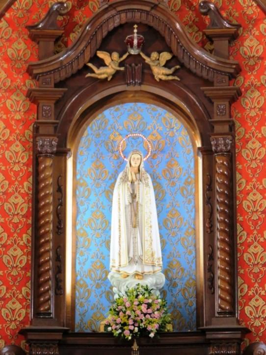 Fotografia colorida, retangular e vertical da imagem da Virgem Maria que está no altar-mor do Santuário Nossa Senhora do Rosário de Fátima, em São Paulo. Ela tem comprido manto branco e auréola dourada, iluminada por pequenas lâmpadas, e as palmas das mãos unidas. Acima de Nossa Senhora, dois anjos seguram uma coroa em prata e veludo vermelho. A imagem está em um nicho em arco, rodeado por estrutura em madeira escura entalhada, com fundo azul e delicadas flores douradas. Em volta, mais uma estrutura em madeira escura entalhada, bem maior, com fundo vermelho e as mesmas flores douradas. Aos pés da virgem, um ramalhete de rosas cor de rosa.