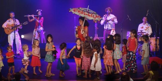 Fotografia colorida com fundo azulado dos cinco componentes do grupo CantaVento (três homens e duas mulheres) no palco, tocando seus instrumentos e cantando, cercado de muitas crianças. Carol Ladeira está à frente do grupo, segurando um microfone e uma sombrinha aberta.