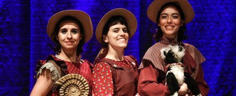 Fotografia colorida em primeiro plano (do peito para cima), das três jovens atrizes que interpretam a cientista Mary Anning no espetáculo Mary e os Monstros Marinhos. Da esquerda para a direita: Thaís Medeiros, Cecília Magalhães e Julia Ianina, todas sorridentes. Elas usam vestidos vermelhos estampados e chapéus de palha Panamá. Thais, à esquerda, segura o fóssil de uma amonita encostado no peito, um tipo de concha marinha com formato espiral; Julia,  à direita, é a mais alta, segura um cachorrinho de pelúcia preto e branco no colo.