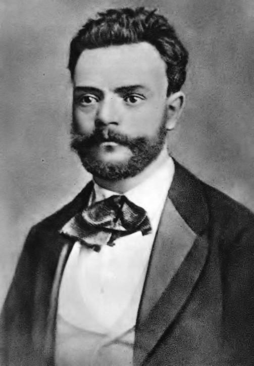 Fotografia em preto e branco, em primeiro plano, do compositor checo Antonín Dvorák. Ele tem os cabelos escuros penteados para trás, olhos expressivos, grande bigode e barba curta. Usa paletó escuro com lapela de cetim, camisa e colete brancos com gravata de laço.