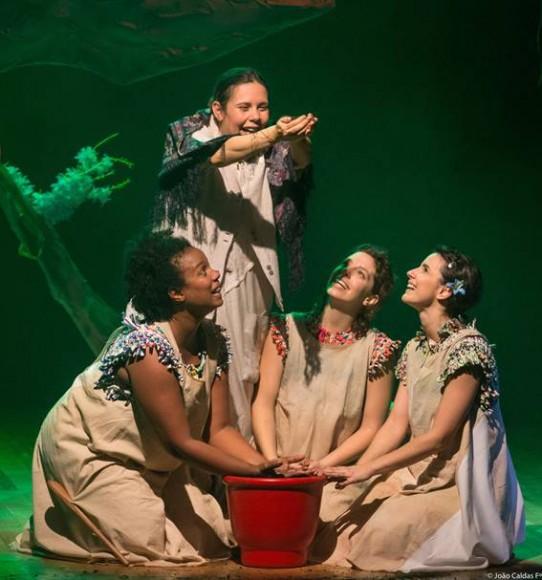 Fotografia colorida das quatro atrizes, três estão ajoelhadas com as mãos apoiadas em um vaso vermelho olhando admiradas para cima, e a outra está em pé com os braços esticados para frente, as mãos em cuia. As três que estão ajoelhadas, uma negra e  três brancas, usam vestidos bege, com mangas curtas e gola de crochê colorido. A mulher que está em pé usa vestido e casaco brancos e xale colorido sobre os ombros. Ao fundo, à esquerda do cenário iluminado com luz verde, parte do tronco e galhos de uma árvore.